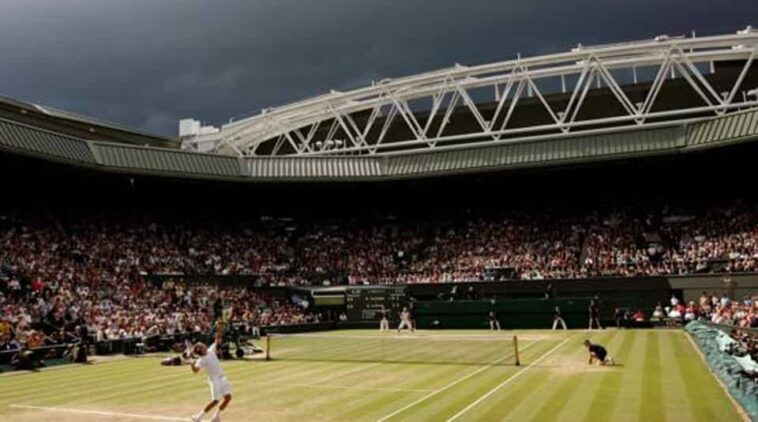 FILE PHOTO: Dark clouds drift over centre court during the finals match between Roger Federer of Switzerland and Rafael Nadal of Spain at the Wimbledon tennis championships in London July 6, 2008.